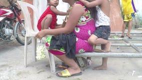 Mãe indigente que é cabelo preparado por suas crianças, implorando na porta portal da igreja video estoque