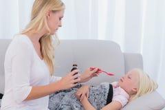 Mãe interessada que dá lhe a medicina da filha fotografia de stock