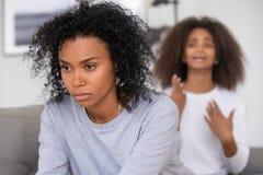 Mãe irritada preta e filha de desculpa no fundo imagens de stock royalty free