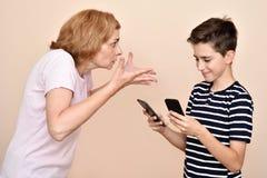 Mãe irritada que discute seu filho de sorriso com dois smartphones fotografia de stock