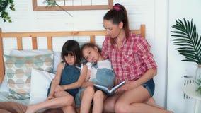 A mãe lê o livro a suas filhas e caem adormecido na cama, família feliz