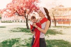 A mãe leva um bebê infantil no estilingue do envoltório no parque primavera Conceito do parenting natural fotografia de stock royalty free
