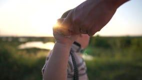 A mãe limpou as mãos de criança pequena no prado com um guardanapo no movimento lento filme