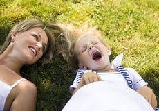 Mãe loura com a filha que tem o divertimento na grama Imagens de Stock