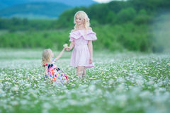 A mãe loura com os vestidos cor-de-rosa coloridos brancos vestindo da filha pequena bonito na camomila coloca, horas de verão apr imagem de stock