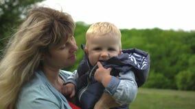 Mãe loura e bebê novos que riem junto ao jogar fora video estoque