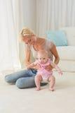 Mãe loura feliz que joga com seu bebê fotografia de stock royalty free