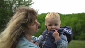 Mãe loura nova feliz que guarda e que anda com seu bebê no movimento lento do parque filme
