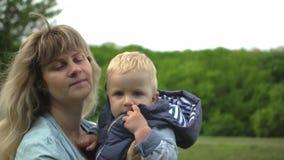 Mãe loura nova feliz que guarda e que joga com seu bebê no movimento lento do parque vídeos de arquivo