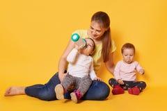 A mãe louro, amando ocupa de suas crianças obedientes pequenas, tem uma refeição, senta-se nos pés da mamã e no assoalho com boca imagens de stock