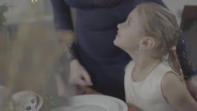 A mãe loving beija a filha bonito entusiasmado feliz do bebê no mordente na decoração festiva da cozinha do jantar de Natal vídeos de arquivo
