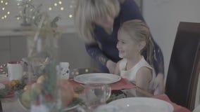 A mãe loving beija a filha bonito entusiasmado feliz do bebê no mordente na decoração festiva do jantar de Natal da cozinha vídeos de arquivo