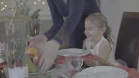 A mãe loving beija a filha bonito entusiasmado feliz do bebê no mordente na decoração festiva do Natal da cozinha do jantar video estoque