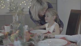 A mãe loving beija a filha bonito feliz entusiasmado do bebê no mordente na decoração festiva do jantar de Natal da cozinha filme