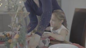 A mãe loving beija a filha entusiasmado bonito feliz do bebê no mordente na decoração festiva do jantar de Natal da cozinha vídeos de arquivo