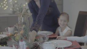 A mãe loving beija a filha entusiasmado bonito feliz do bebê no mordente na decoração festiva do jantar de Natal da cozinha video estoque