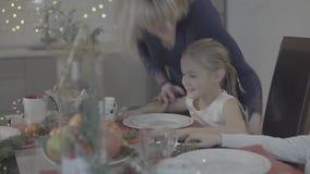 A mãe loving beija a filha entusiasmado feliz bonito do bebê no mordente na decoração festiva do jantar de Natal da cozinha vídeos de arquivo