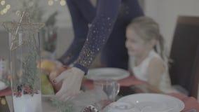 A mãe loving beija a filha feliz entusiasmado bonito do bebê no mordente na decoração festiva do jantar de Natal da cozinha vídeos de arquivo