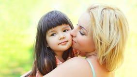 Mãe loving feliz do retrato que beija a criança fora no verão Foto de Stock