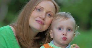 Mãe loving que beija a criança vídeos de arquivo