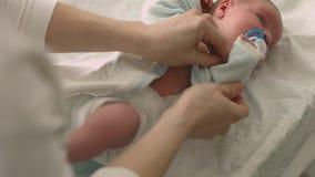 A mãe loving veste seu bebê recém-nascido na tabela em mudança video estoque