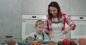 Mãe madura com seus 9 anos do filho que cozinha junto na cozinha, atmosfera bonito video estoque