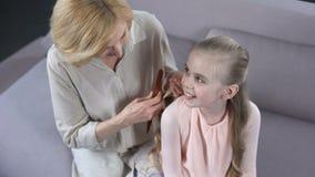 Mãe madura de inquietação que penteia o cabelo louro da filha, tempo da beleza, relacionamento filme