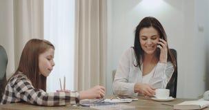 Mãe madura ocupada que trabalha da casa no café bebendo da manhã e que passa o tempo com suas três crianças que têm video estoque