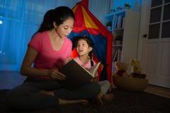 Mãe magro que guarda a história de horas de dormir faladora do livro Foto de Stock Royalty Free