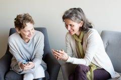 Mãe mais idosa e filha que sorriem com smartphones Foto de Stock