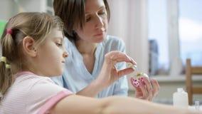 A mãe mostra a sua filha como decorar o ovo com sparkles para o feriado com um começo da escova e da menina seus próprios video estoque