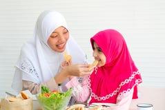 A mãe muçulmana e sua filha estão comendo cookies junto com uma bacia da salada vegetal no fundo branco imagens de stock royalty free