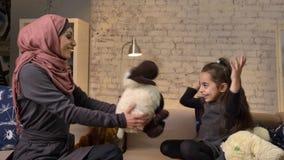 A mãe muçulmana nova no hijab dá-lhe carneiros da peluche da filha, família que senta-se em um sofá, idílio, conforto home no filme