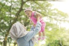 Mãe muçulmana que joga com a filha no parque fotos de stock