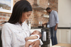 A mãe no portátil guarda o filho recém-nascido como o pai Makes Meal Foto de Stock Royalty Free