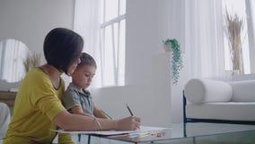 A mãe no revestimento amarelo e o filho no t-shirt sentam-se na tabela e tiram-se junto lápis da cor no papel Inf?ncia feliz filme