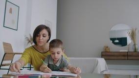 A mãe no revestimento amarelo e o filho no t-shirt sentam-se na tabela e tiram-se junto lápis da cor no papel Inf?ncia feliz video estoque