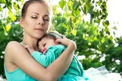 A mãe nova abraçou a criança na natureza fotos de stock