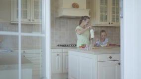 Mãe nova adorável e pouco cozinheiro bonito da filha na cozinha junto Fam?lia feliz Mamã e filha do relacionamento video estoque