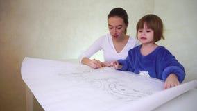 A mãe nova ajuda a filha com desenho, meninas concentradas que sentam-se na sala bem iluminado discutindo a ocupação filme