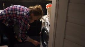 A mãe nova alegre, energética gerencie sobre uma máquina de lavar, seleciona o modo ao guardar seu bebê em seus braços matriz vídeos de arquivo