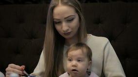 A mãe nova alimenta uma menina com um queijo de Suluguni video estoque