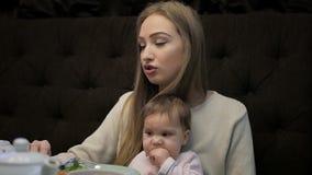 A mãe nova alimenta uma menina com um queijo de Suluguni filme