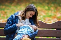 Mãe nova, amamentando seu bebê recém-nascido exterior no Fotos de Stock