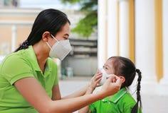 Mãe nova asiática que veste a máscara protetora para sua filha quando parte externa contra a PM 2 poluição do ar 5 na cidade de B foto de stock royalty free
