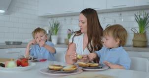 Mãe nova bonita com os dois filhos das crianças no cozinheiro claro branco do kuna com hamburgueres filme