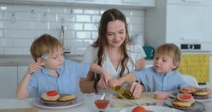 Mãe nova bonita com os dois filhos das crianças no cozinheiro claro branco do kuna com hamburgueres vídeos de arquivo