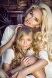 A mãe nova bonita com sua filha vestiu-se na roupa da mola e nas grinaldas das flores Imagem de Stock Royalty Free