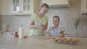 Mãe nova bonita e pouco cozinheiro bonito da filha na cozinha junto Fam?lia feliz Mam? do relacionamento e video estoque