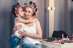Mãe nova bonita e sua filha com encrespadores de cabelo imagem de stock royalty free